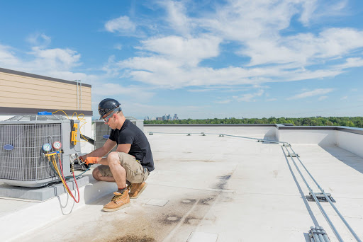 Hvac worker servicing an air conditioner unit with blue sky copyspace